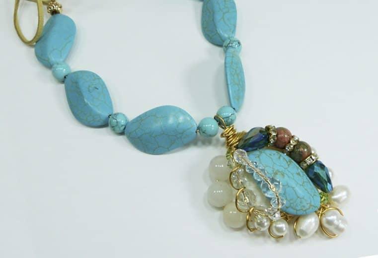 Colgante de gemas turquesas con centro de turquesa rodeado perlas de rio, cristales y unaquitas