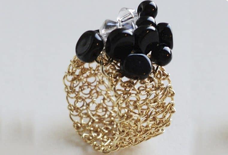 anillo tejido a mano con hilos de oro, cristales y piedras negras