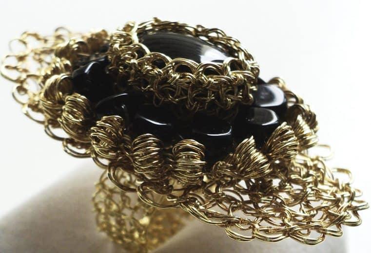anillo tejido crochet con hilos de oro y piedras negras