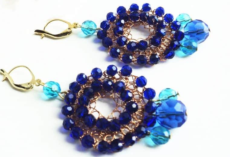 Aretes con centro abierto y cristales celestes y azules tejidos con alambre de oro