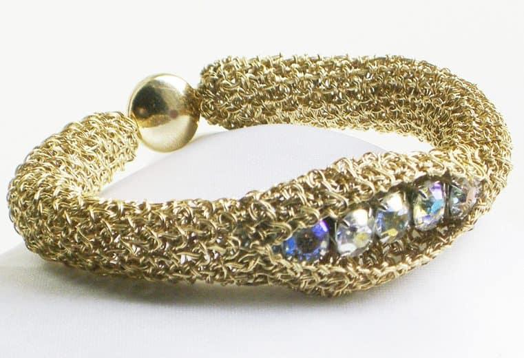 Brazalete tejido con alambre de oro y cristales swarovski en el centro de la pieza