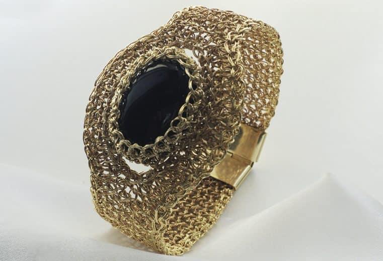 Brazalete tejido con alambre de oro y obsidiana en el centro