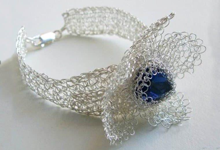 Brazalete tejido con alambre de plata con forma de flor y cristal azul en el centro