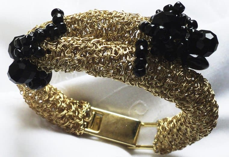 Brazalete tubular tejido con alambre de oro y cuentas facetadas negras en los extremos